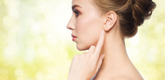 Beautiful woman pointing finger to her ear. Health, people and beauty concept - beautiful young woman pointing finger to her ear over yellow holidays lights royalty free stock images