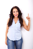 Beautiful woman pointing finger up against white background Stock Images