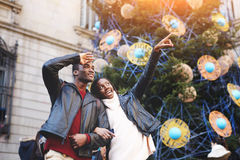 Beautiful woman pointing with her finger something interesting, young lovers standing against Christmas tree with decorations on b Royalty Free Stock Photography