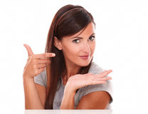 Beautiful woman pointing and holding her palm up Stock Photo