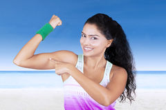 Beautiful woman pointing muscle at beach Royalty Free Stock Photo