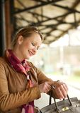 Beautiful woman pointing to her watch outdoors Stock Photo