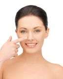 Beautiful woman pointing to nose Royalty Free Stock Image