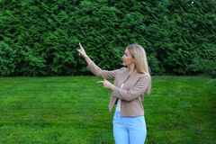 Beautiful woman points with both hands on potential place to adv Stock Photo