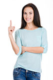 Beautiful woman points finger up. Stock Photography