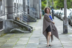 Beautiful woman in a poncho standing on the street. Stock Photos