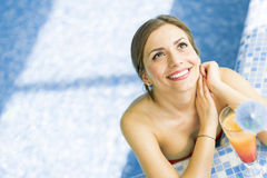 Beautiful woman in a pool with a cocktail Stock Images