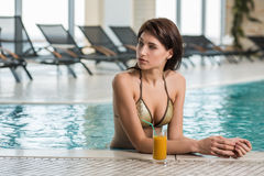 Beautiful woman in a pool with a cocktail next to her Stock Photos