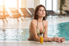 Beautiful woman in a pool with a cocktail next to her royalty free stock images