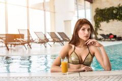 Beautiful woman in a pool with a cocktail next to her stock photo