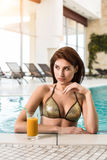 Beautiful woman in a pool with a cocktail next to her Stock Photography