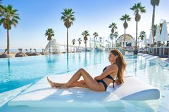 Beautiful woman on pool hammock at resort Stock Images
