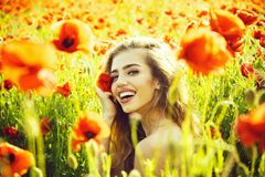 Beautiful woman on poppy field with long hair royalty free stock photos