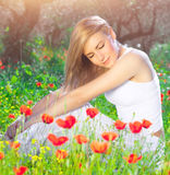 Beautiful woman on poppy flower field stock photography