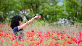 Beautiful woman with poppy flowers in spring stock footage