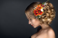 Beautiful woman portrait with autumn flowers in hair. With nice hairstyle Royalty Free Stock Image
