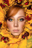 Beautiful woman portrait with autumn leaves. With colorful make up Stock Images