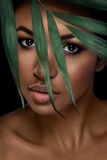 Beautiful woman portrait on black background. Young afro girl posing with green leaves and closed eyes. Gorgeous make up. Pure skin Stock Photography