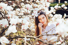 Beautiful woman portrait in blossoming magnolia tree flowers in a sunny day of spring. Stock Photo