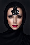 Beautiful woman portrait in east style. Beautiful woman portrait in east style with headscarf and jewelry on face Royalty Free Stock Image