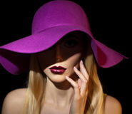 Beautiful woman portrait. Fashion art photo. Beautiful young model with mauve hat on colored background, studio shot Stock Image