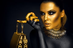 Beautiful woman portrait in gold and black colors. On black background Royalty Free Stock Photos