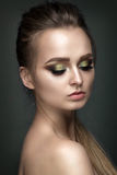 Beautiful woman portrait on grey background. With green eye shadows Stock Photography