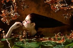 Beautiful woman portrait with Leaves and branches in autumn wate Royalty Free Stock Photography