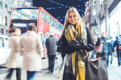 Beautiful woman portrait in London during Christmas time. Beautiful woman portrait in London on Christmas time. Blonde woman, on her early twenties, wearing warm Stock Photo