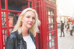 Beautiful woman portrait in London with red phone booth Royalty Free Stock Image