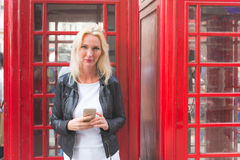 Beautiful woman portrait in London with red phone booth Royalty Free Stock Photo