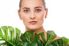 Beautiful woman portrait with tropical plant. Beautiful woman portrait with natural makeup and a tropical plant in front of her royalty free stock photos