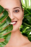 Beautiful woman portrait with tropical plant. Beautiful woman portrait with natural makeup and a tropical plant in front of her face stock images
