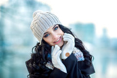 Beautiful woman portrait. Nice smile. Outside photo shoot. Winter. A girl is in warm clothes and with hat on head. Nice make up and curly hairs Royalty Free Stock Photography