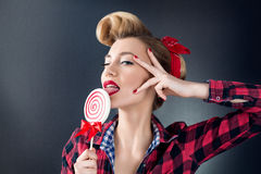 Beautiful woman portrait in pin-up style with candy in hand. Nice makeup. Interesting hairstyle Royalty Free Stock Image