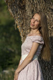 Beautiful woman portrait in a pink dress in front of a tree with ivy. Stock Image