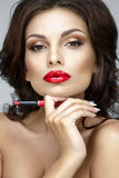 Beautiful woman portrait with red lips. Beautiful woman portrait with red lips and with lipstick in hand Stock Photography