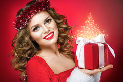 Beautiful woman portrait with red lips on red background. Beautiful woman portrait on red background. Christmas lady with a gift Stock Photos