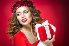 Beautiful woman portrait with red lips on red background. Beautiful woman portrait on red background. Christmas lady with a gift Royalty Free Stock Photos