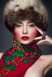 Beautiful woman portrait in russian style with fur hat and scarf. Russian beauty Royalty Free Stock Images