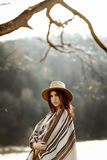 Beautiful woman portrait wearing hat and poncho at tree near river, american outfit, boho concept Stock Photography