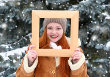 Beautiful woman portrait on winter outdoor, look through wooden frame, snowy fir trees in forest, long red hair, wearing a sheepsk. In coat stock images