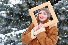 Beautiful woman portrait on winter outdoor, look through wooden frame, snowy fir trees in forest, long red hair, wearing a sheepsk Royalty Free Stock Image