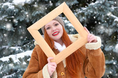 Beautiful woman portrait on winter outdoor, look through wooden frame, snowy fir trees in forest, long red hair, wearing a sheepsk Royalty Free Stock Photo