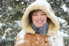 Beautiful woman portrait on winter outdoor, snowy fir trees in forest, long red hair, wearing a sheepskin coat Stock Images
