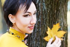 Beautiful woman portrait with yellow leaf on tree bark background, autumn forest, fall season Stock Photos