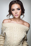 Beautiful woman portrait. Young lady posing in warm sweater. Nice makeup and hairstyle. Studio photo shoot Royalty Free Stock Images