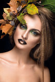 Beautiful woman portrait. Young model posing on black background with. Autumn leaves. Gorgeous make up Royalty Free Stock Photos