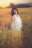 Beautiful woman poses in a field Stock Photography