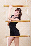 Beautiful woman poses holding bamboo rope ladder. Royalty Free Stock Photography